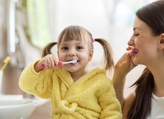 A little girl brushing her teeth with her mom