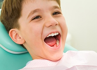 Young boy smiling in a dental chair.