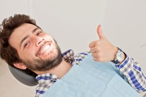man reclining in dental chair smiling