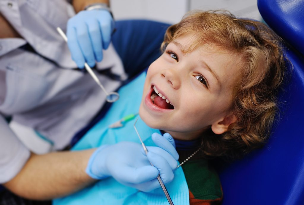 A smiling little boy in the dental chair