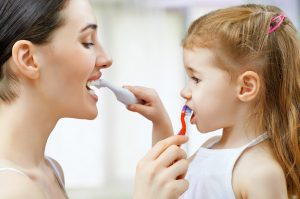 Mother and young daughter brush each other's teeth